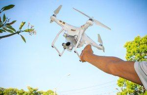 Drone hovering away from a man's outstretched hand into the sky
